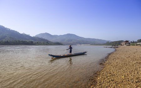 Fisherman standing on wooden boat working on his fishing net on Mae Khong river in northern Thailand, mountain view outdoor day light, tourism background