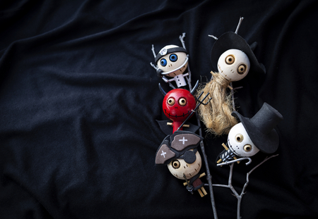 Ghost wooden doll collection on dark background, Halloween decoration item on black fabric texture background Stock Photo