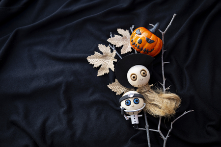 Happy Halloween card concept, cute wooden witch and doctor doll with funny pumpkin on black fabric texture background