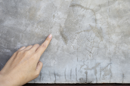 Girl hand point on grey cement wall background, construction concept background Banque d'images