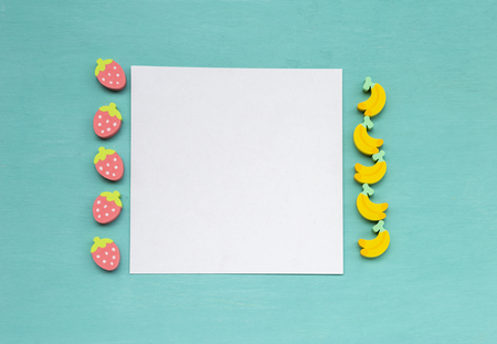 Blank white paper card with fruit shape eraser on blue texture background