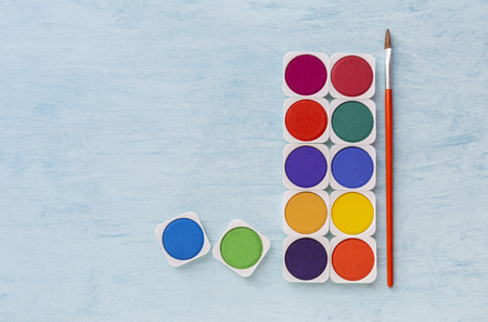 Colorful watercolour tablet set with paint brush on blue texture background, education and art object concept