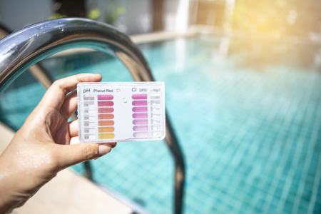 Water testing test kit in girl hand over blurred swimming pool with warm light, summer outdoor day light Stockfoto