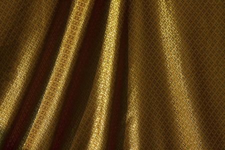 Closeup gold pattern fabric texture background, waving gold Thai style fabric pattern background