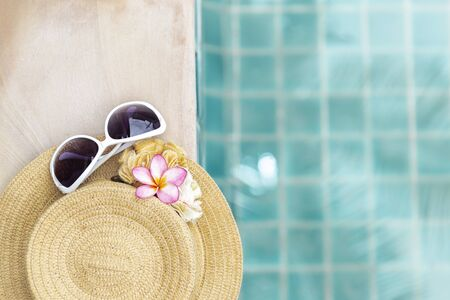 Sumer vacation and holiday concept background, design women sunglasses on beach hat over blurred blue swimming pool water background, outdoor day light