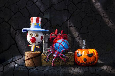 Halloween concept background, wooden bozo ghost with color yarn spider in treasure box and halloween pumpkin on abstract craked soil background