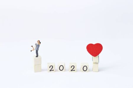 Miniature happy couple on wooden cube with red heart clip, Happy New Year 2020