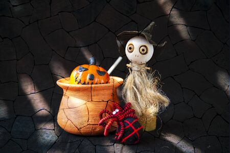 Halloween concept background, Cute little wooden witch doll with black and red yarn spider with halloween pumpkin in clay pot over abstract brick wall background, decorate item Reklamní fotografie