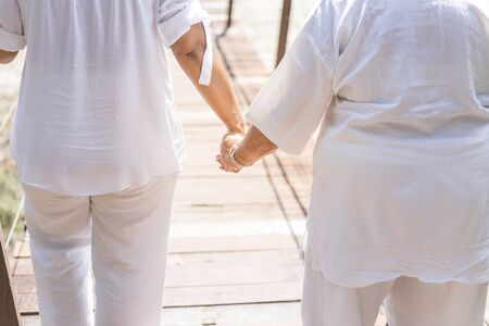 Girl holding hand crossing the bridge, girl in white cloths holding elderly woman, health care and elderly care Stok Fotoğraf - 132859104