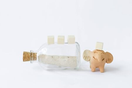 Smiling elephant clay doll with letter in glass bottle and blank wooden cube isolate on white background, message in bottle, love letter, secret letter