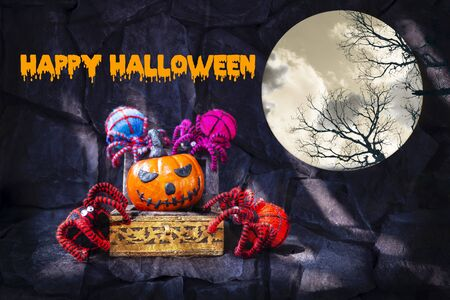Happy Halloween concept background, Halloween pumpkin in wooden treasure box with group of colourful yarn spider, decorate item