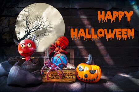 Happy Halloween concept background, Little wood red devil with blue and red yarn spider in treasure and smiling pumpkin over abstract old brick wall texture background Stok Fotoğraf - 132859140