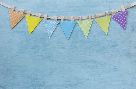 Colourful fabric vintage party flag on blank blue texture background, fabric color triangle flag on blue background Stok Fotoğraf - 132922398