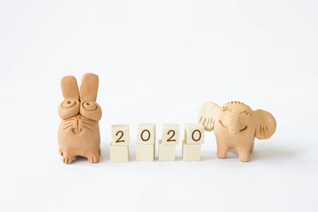 Happy New Year 2020, letter on wooden cube with lovely rabbit and elephant clay friend isolate on white background, smiling welcome to year 2020