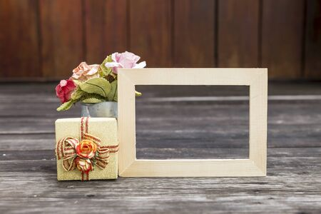 Wooden picture frame with gift box and paper flower on wooden floor, new yar and christmas gift concept Stok Fotoğraf