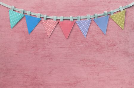 Colorful vintage fabric party flag on pink texture background, celebrate and party background