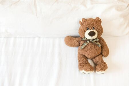 Fluffy brown teddy bear lying down on the bed alone with space on white bed sheet Stok Fotoğraf