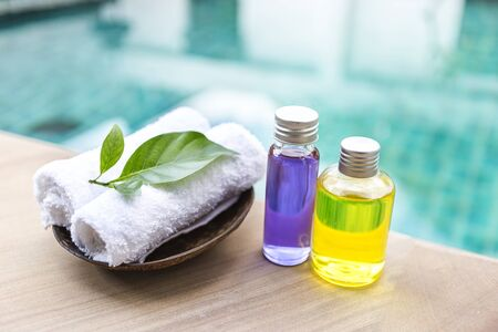 Spa concept background, Massage oil in glass bottle with white hand towel on swimming pool edge with space on blurred blue water background, outdoor day light Stok Fotoğraf