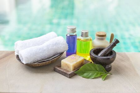 Spa treatment set concept, massage oil with nature soap bar with white hand towel and wooden mortar over blurred blue water background, outdoor day light