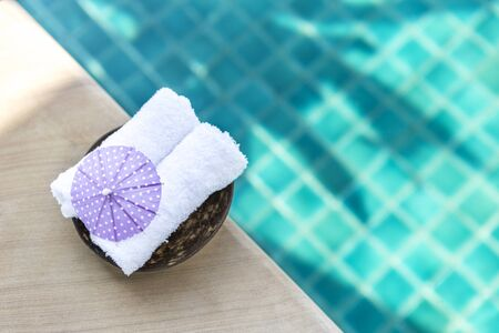 White hand towel with purple paper umbrella on swimming pool edge with space on blurred blue water background, outdoor day light Stok Fotoğraf