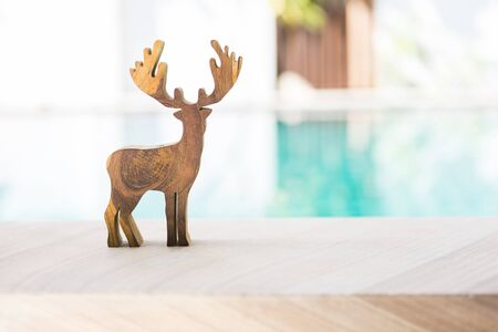 Wooden reindeer on swimming pool edge over blurred blue water background, outdoor day light, Christmas concept background, decoration item Stok Fotoğraf