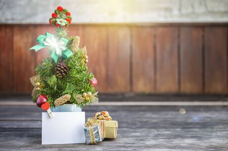 Beautiful mini Christmas tree with colorful decoration item and blank white paper card and gift boxes over blurred wood background, outdoor day light