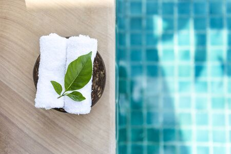 White hand towel with beautiful fresh green leaf on swimming pool edge with space on blurred blue water background, outdoor day light