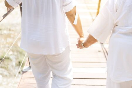 Girl holding hand crossing the bridge, girl in white cloths holding elderly woman, health care and elderly care