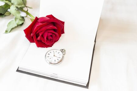 Red rose with vintage watch on blank white notebook with space on white sheet background, valentine concept, beautiful time Stok Fotoğraf