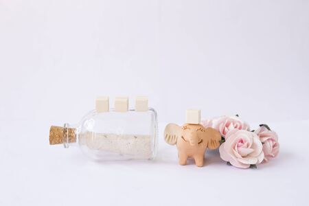 Happy smiling elephant clay doll with message in glass bottle, wooden cube withe happy doll and rose paper flower, valentine concept Stok Fotoğraf