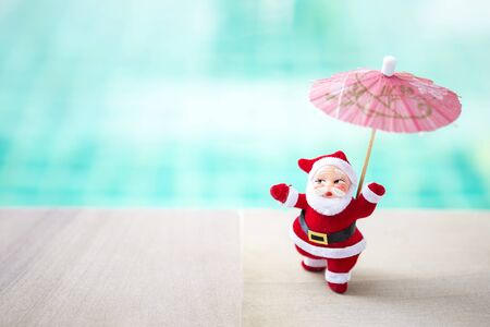 Santa with paper umbrella over blurred blue water background, Christmas concept