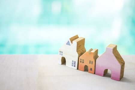 Design miniature wooden house over blurred blue water background, outdoor day light, property and real estate business concept