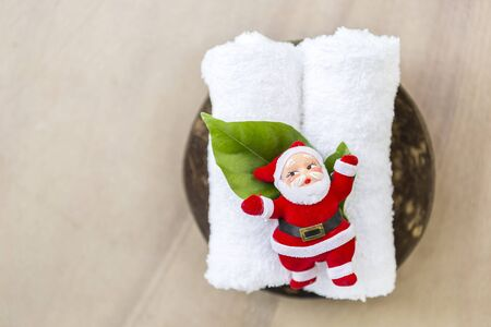 Santa on white towel with space on blurred stone texture background, Christmas concept, happy holiday relaxing