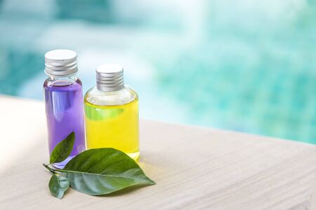 Purple and yellow massage oil with herbal leaf over blurred blue water backbround, outdoor day light, spa concept background Stok Fotoğraf