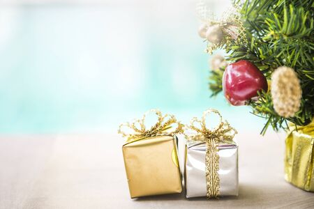 Gold and silver gift box with Christmas tree over blurred background, Festive sason concept background