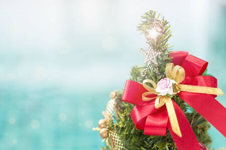 Happy Christmas background, red ribbon on christmas tree with shiny star over blurred blue background Stok Fotoğraf