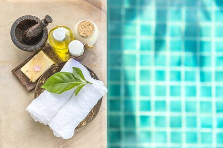Spa concept background, white towel with nature soap and massage oil and wooden mortar with space on blue swimming pool water background