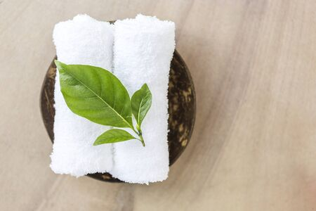 Beautiful fresh green leaf on white towel on coconut shell with space on stone texture background, spa concept background