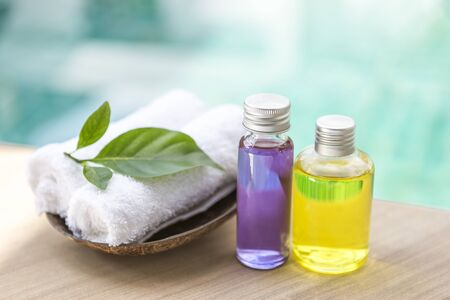 Spa concept background, Yellow and purple oil in glass bottole with green leaf on white hand towel on swimming pool edge with space on blurred blue water background, outdoor day light