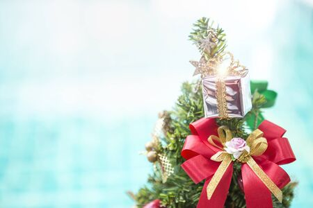 Christmas concept background, Silver gift box with colorful ribbon on Christmas tree over blurred blue water background, outdoor day light, festive season concept background