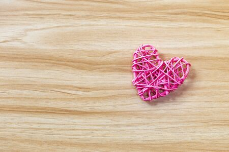 Design pink wooden heart on wood texture background, love and romance concept, valentine idea background