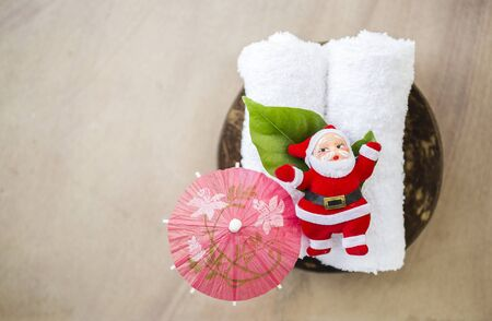 Holiday retreat concept, Santa with red paper umbrella on white hand towel with space on stone texture background, outdoor day light, Christ mas relaxation, holiday time