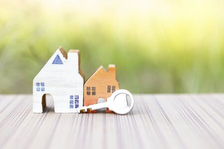 Miniature wooden house with steel key over blurred green garden background, outdoor day light, property and real estate business concept, house loan, new house