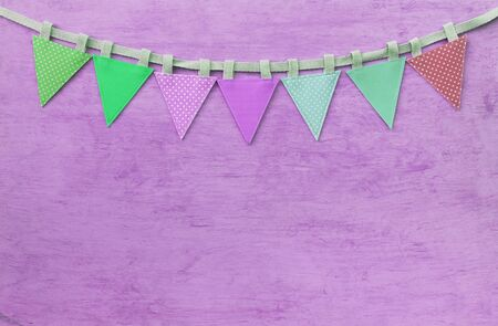 Vintage fabric triangle party flag on purple texture background, festive and celebrate concept background, vintage tone style