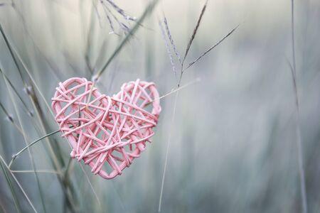 Vintage wooden pink heart over blurred garden background, love and romance concept, valentine background idea