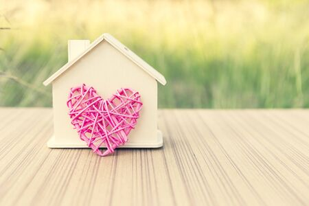 Wooden house with design wooden pink heart, house of love, vintage filter, outdoor day light
