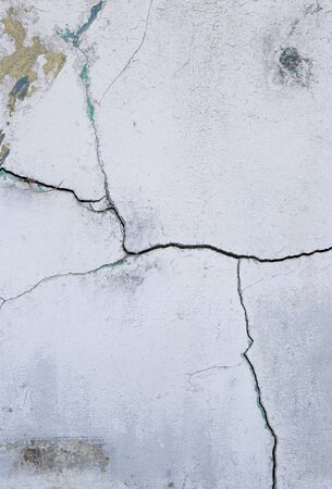 Abstract crack texture on old white paint cement wall, vertical style, outdoor day light, construction problem Stok Fotoğraf