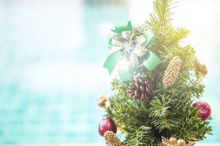 Christmas background idea, Christmas tree with green ribbon over blurred blue water background, outdoor day light