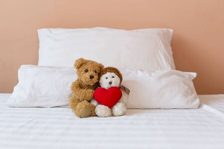 Cute little brown and white teddy bear holding red heart sitting in the bed, love and romance concept, valentine background