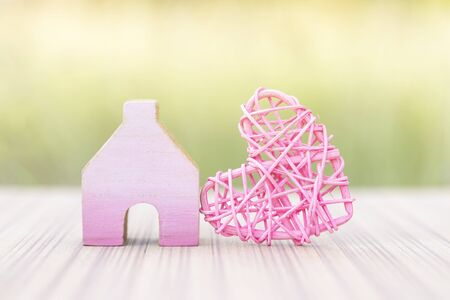 Cute pink miniature wooden house with pink wooden heart design over blurred green garden background, outdoor day light, house of love, love and romance concept